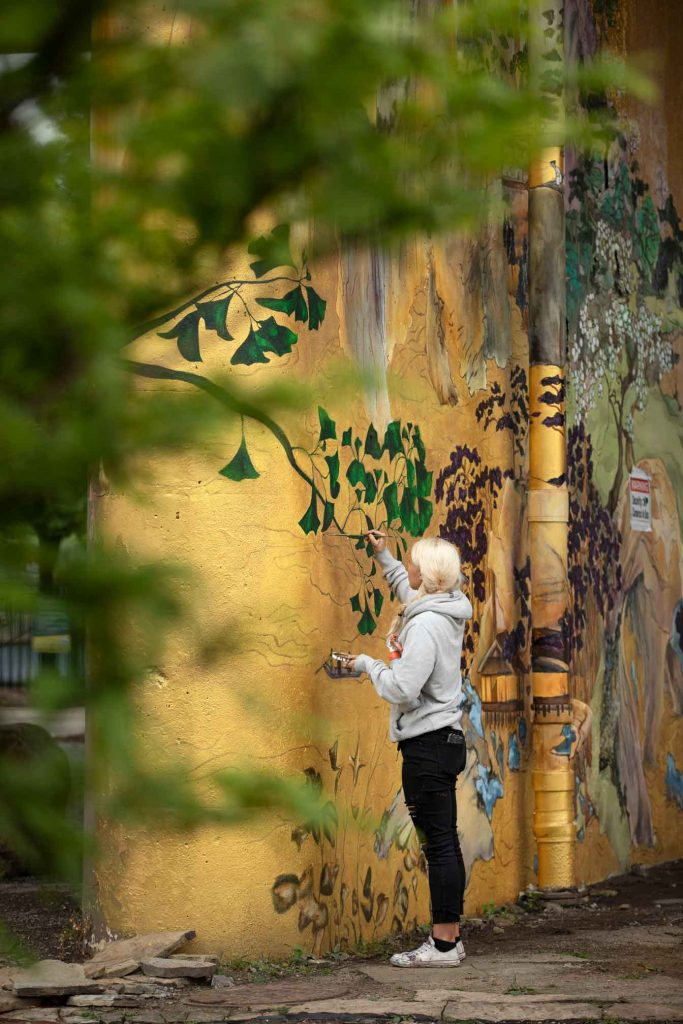 Muralist painting in Ping Tom Park Chicago