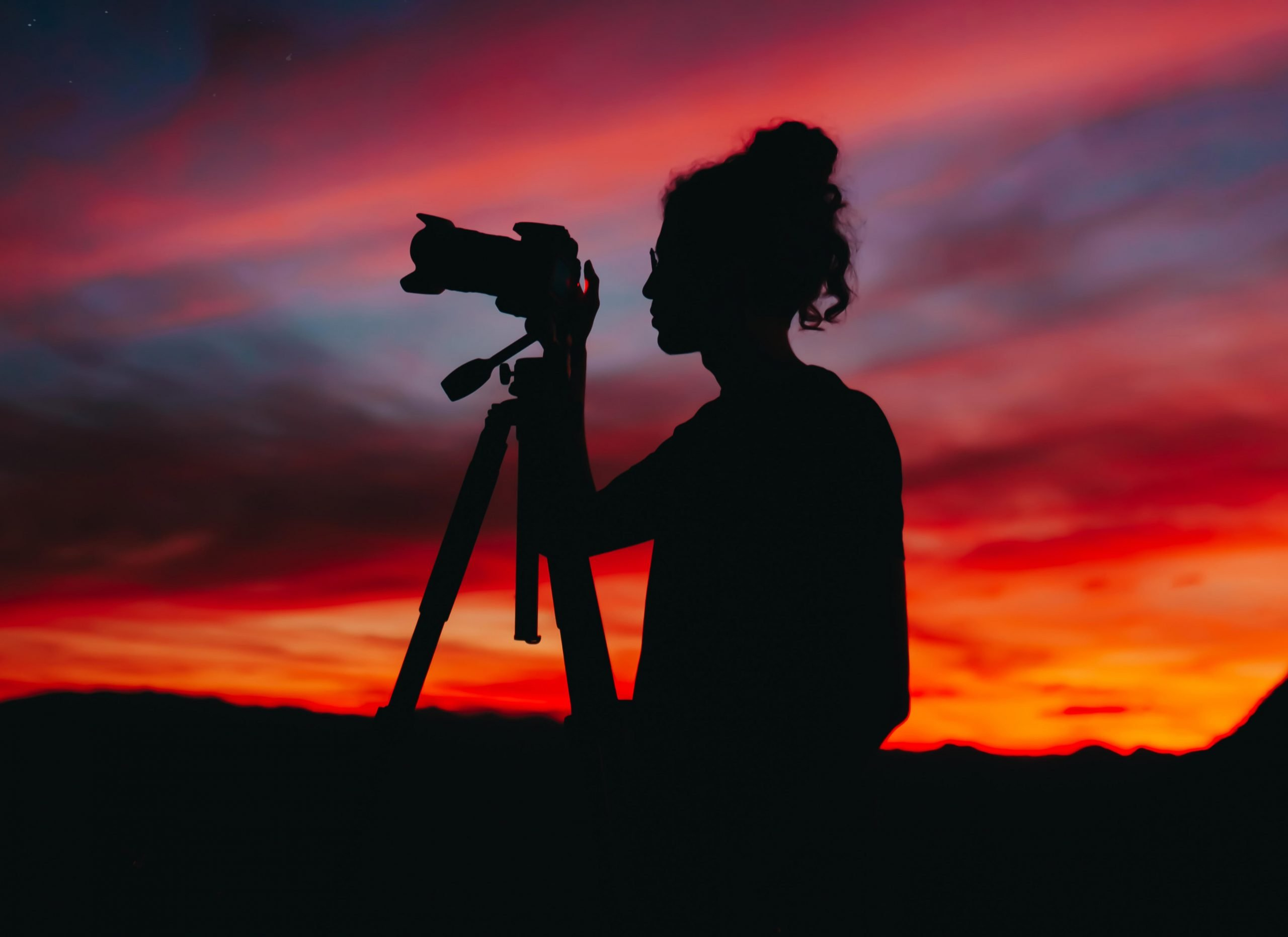 Photo of a woman taking a picture of a sunset.