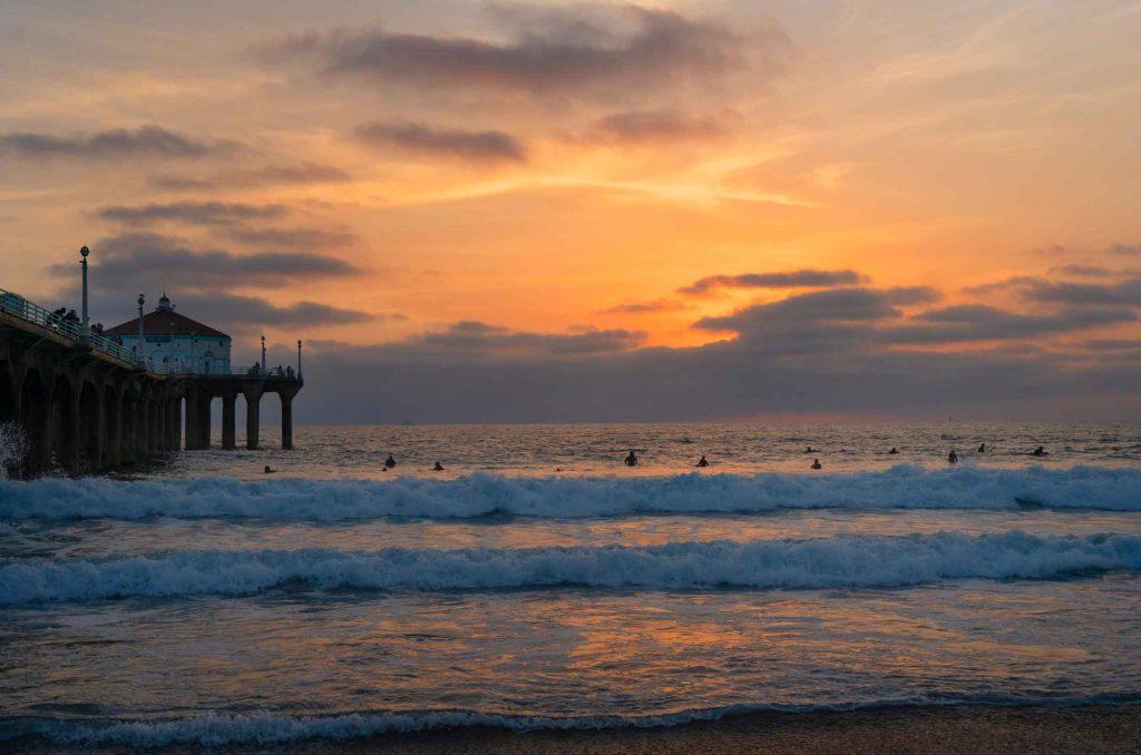 Surfers at sunset in Manhattan Beach, California - California Cities